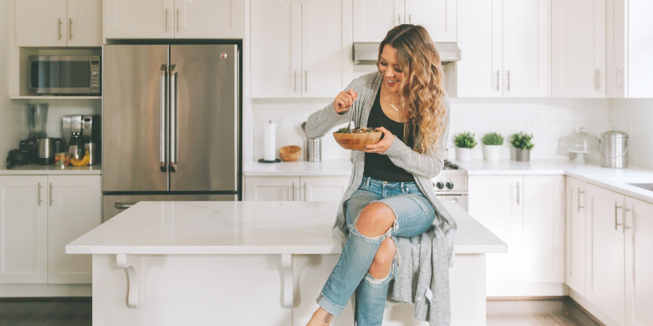 a-woman-eating-a-salad-while-sitting-on-the-kitchen-counter_t20_xR0peB