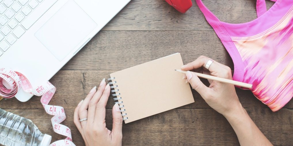 overhead-view-of-woman-hand-writing-on-notebook-with-laptop-and-fitness-items-on-wooden-table_t20_OpVZdL